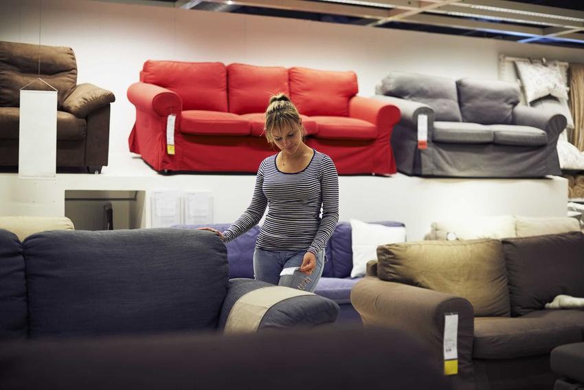 Kobieta przeglądająca kanapy w sklepie meblowym, a także informacje, gdzie najlepiej kupić meble do salonu krok po kroku