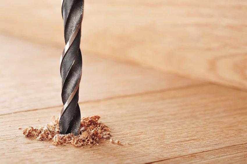 Wiertło wiertarki stołowej wycelowane w kawałek drewna, a także wiertarka stołowa krok po kroku, rodzaje, ceny, producenci