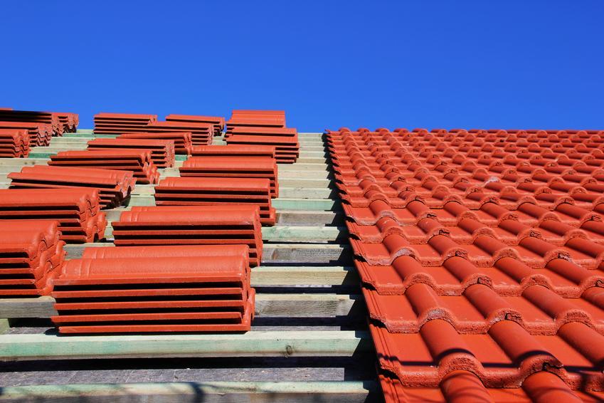 Montaż dachówki ceramicznej na prostym dachu dwuspadowym. Dachówka karpiówka o normalnym fomacie. Brak lukarn i dodatkowych nieregularności w kształcie dachu
